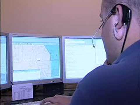 image of dispatcher taking calls and watching computer monitors